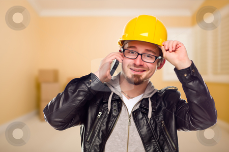 Young Contractor Wearing Hard Hat on Cell Phone In House stock photo, Young Contractor Wearing Hard Hat on Cell Phone Inside Empty House. by Andy Dean