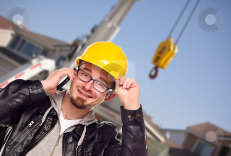 Young Cunstruction Worker on Cell Phone In Front of Crane stock photo, Young Contractor Wearing Hard Hat on Cell Phone In Front of Utility Crane. by Andy Dean