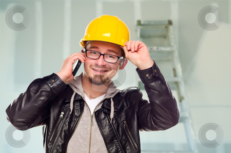 Contractor in Hard Hat on Cell Phone In Unfinished House stock photo, Young Contractor Wearing Hard Hat on Cell Phone In Unfinished House with Drywall and Ladder in the Background. by Andy Dean