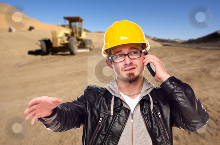 Young Cunstruction Worker on Cell Phone in Dirt Field with Tract stock photo, Young Cunstruction Worker on Cell Phone in Dirt Field with Tractor in the Background. by Andy Dean
