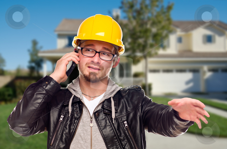 Contractor Wearing Hard Hat on Phone In Front of House stock photo, Young Contractor Wearing Hard Hat on Cell Phone In Front of House. by Andy Dean