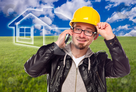 Contractor in Hard Hat in Front of Ghosted House and Grass Field stock photo, Contractor in Hard Hat on Cell Phone in Front of Ghosted House, Grass Field and Blue Sky with Clouds. by Andy Dean