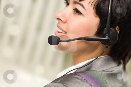 Profile of Attractive Young Mixed Race Woman Smiles Wearing Head stock photo, Profile of an Attractive Young Mixed Race Woman Smiles Wearing Headset In An Office Setting. by Andy Dean