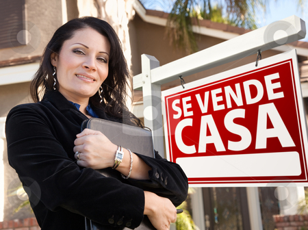 Female Hispanic Real Estate Agent, Se Vende Casa Sign and House stock photo, Proud, Attractive Hispanic Female Agent In Front of Spanish Se Vende Casa Real Estate Sign and House. by Andy Dean