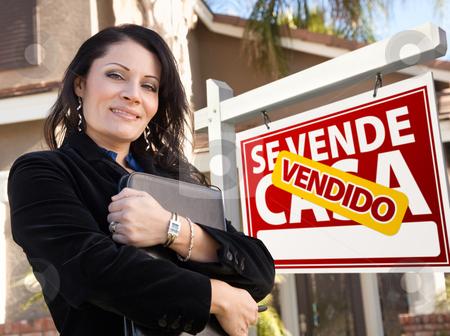 Female Hispanic Real Estate Agent, Vendido Se Vende Casa Sign an stock photo, Proud, Attractive Hispanic Female Agent In Front of Spanish Vendido Se Vende Casa Real Estate Sign and House. by Andy Dean