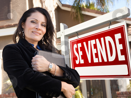 Female Hispanic Real Estate Agent, Se Vende Sign and House stock photo, Proud, Attractive Hispanic Female Agent In Front of Spanish Se Vende Real Estate Sign and House. by Andy Dean