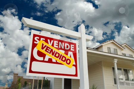 Vendido Se Vende Casa Spanish Real Estate Sign and House stock photo, Vendido Se Vende Casa Spanish Real Estate Sign and House and Blue Sky with Clouds. by Andy Dean
