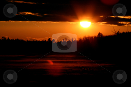 Sun setting behind a frozen Saskatchewan lake stock photo, Sun setting behind a frozen Saskatchewan lake by Mark Duffy