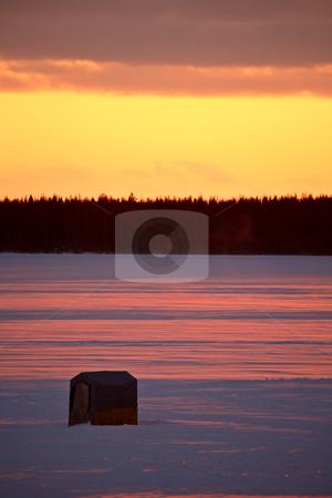 Icefishing shack on frozen lake at sunset stock photo, Icefishing shack on frozen lake at sunset by Mark Duffy