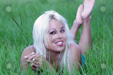 Sexy Blonde Lying in a Grassy Field (5) stock photo, A beautiful young platinum blonde with a bright, warm smile lying in a grassy field. by Carl Stewart