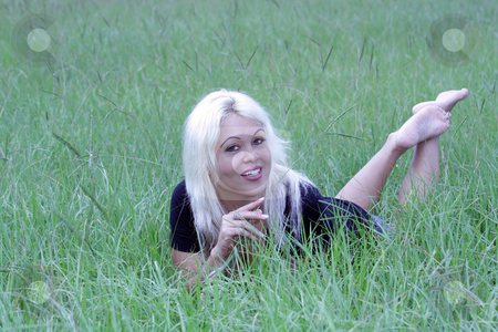 Sexy Blonde Lying in a Grassy Field (8) stock photo, A beautiful young platinum blonde with a bright, warm smile lying in a grassy field. by Carl Stewart