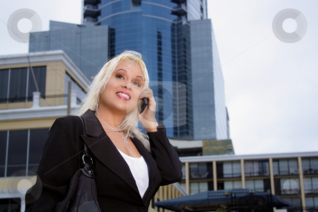 Beautiful Businesswoman Outdoors (1) stock photo, Low-angle shot of a lovely platinum-blonde businesswoman talking on her cellular phone outdoors with a high-rise office building behind her. by Carl Stewart