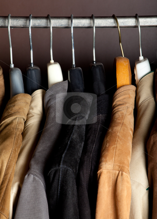 Wardrobe closeup vertical shot stock photo, a closeup of some jackets on hangers in a wardrobe by Jerax