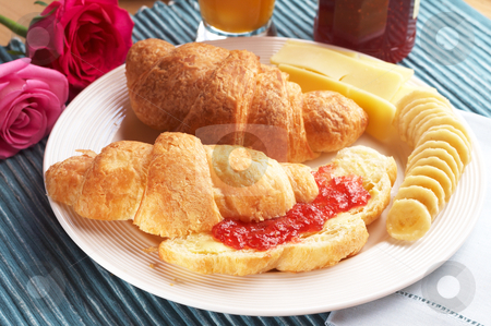 Croissant with cheese stock photo, Breakfast plate with freshly baked croissants filled with jam and served with sliced bananas and cheddar cheese by Elena Weber (nee Talberg)