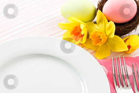 Easter Table Setting stock photo, A pastel pink place setting decorated with Easter eggs and  yellow daffodils is a perfect background with ample copy space by Karen Sarraga