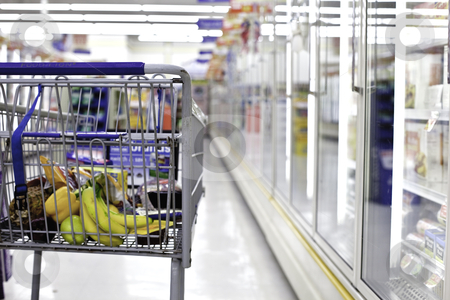 Grocery shopping cart  stock photo, partial view from behind of a grocery shopping cart partially filled with food with a shallow depth of field isolating the cart by Joshua Minso