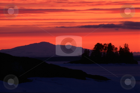 Sunset/sunrise stock photo, Sunset / sunrise in winter.Red sky and snow mountain by Ingvar Bjork