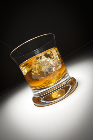 Glass of Whiskey and Ice Under Spot Light. stock photo, Glass of Whiskey or Other Alcoholic Drink and Ice Under Spot Light. by Andy Dean