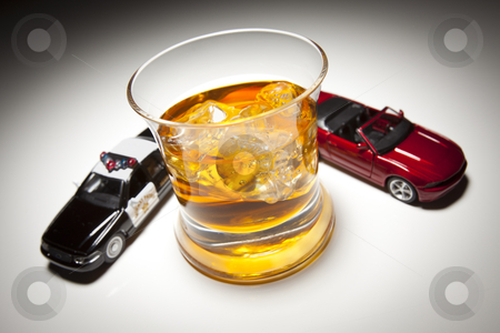 Police and Sports Car Next to Alcoholic Drink stock photo, Police and Sports Car Next to Alcoholic Drink Under Spot Light. by Andy Dean
