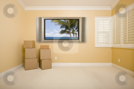 Flat Panel Television on Wall in Empty Room with Boxes stock photo, Flat Panel Television on Wall with Tropical Scene in Empty Room with Boxes. by Andy Dean