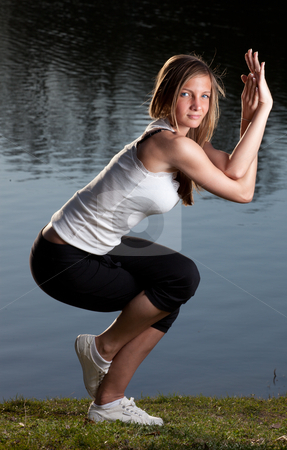 Young woman yoga lake stock photo, a young woman in a yoga stance in front of a lake by Jerax