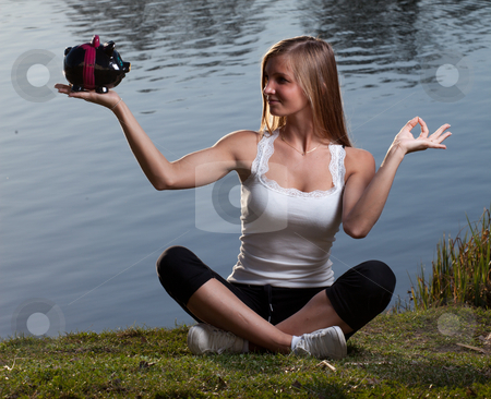 Young woman meditation piggy bank stock photo, a young woman with a piggy bank meditating in front of a lake by Jerax