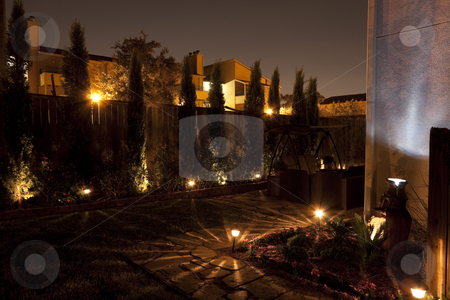 Backyard Garden stock photo, A patio garden or small backyard garden at night with pathway lights by Kevin Tietz