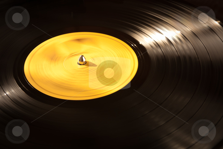 Vinyl Record Playing stock photo, An old vinyl LP playing on a turntable. Good background for music designs. by pcusine