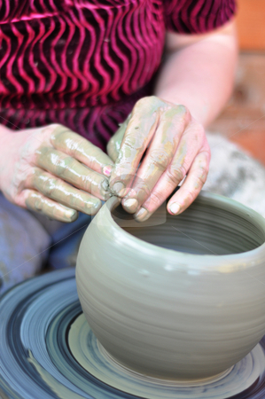 Hands of a potter stock photo, The hands of a potter creating an earthen jar  by Tudor Antonel adrian