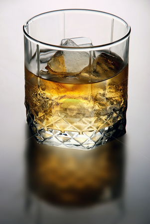 Glass of whiskey stock photo, glass of whiskey with ice cubes by sutike