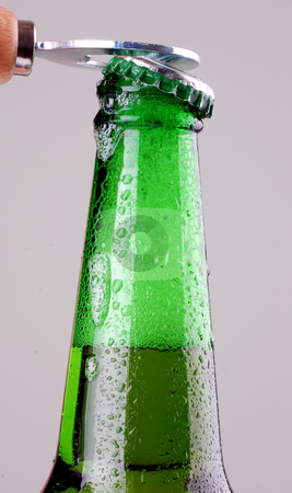 Beer bottle being opened stock photo, Green beer bottle being opened by sutike