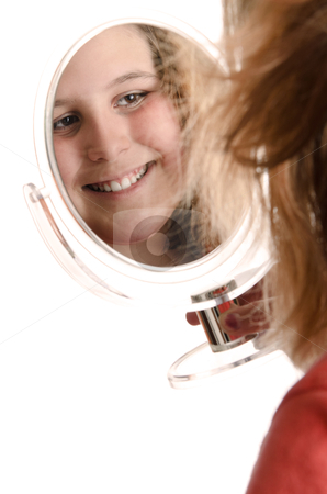 Preteen Looking In Mirror stock photo, A smiling preteen girl is looking at herself in a small mirror, isolated against a white background. by Richard Nelson