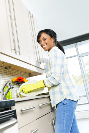 Happy young woman washing dishes stock photo, Happy smiling young black woman enjoying washing dishes in kitchen by Elena Elisseeva