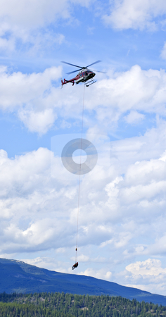 Rescue helicopter in mountains stock photo, Rescue helicopter rescuing person by airlifting dangling on rope in Alberta Canada by Elena Elisseeva