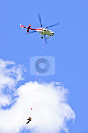 Rescue helicopter stock photo, Rescue helicopter rescuing person by airlifting dangling on rope by Elena Elisseeva
