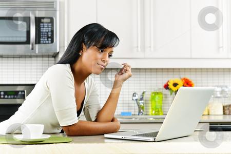 Woman using computer in kitchen stock photo, Thoughtful black woman using computer in modern kitchen interior by Elena Elisseeva