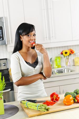 Young woman tasting vegetables in kitchen stock photo, Smiling black woman tasting vegetables in modern kitchen interior by Elena Elisseeva