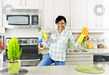Young woman cleaning kitchen stock photo, Smiling young black woman dancing and enjoying cleaning kitchen by Elena Elisseeva