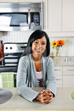 Woman in kitchen stock photo, Smiling black woman in modern kitchen interior by Elena Elisseeva