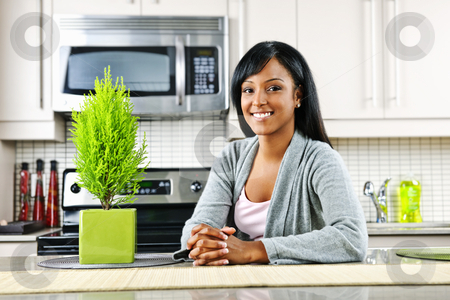 Young woman in kitchen stock photo, Smiling black woman in modern kitchen interior by Elena Elisseeva