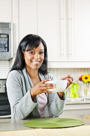 Woman having breakfast stock photo, Smiling black woman having breakfast in modern kitchen interior by Elena Elisseeva