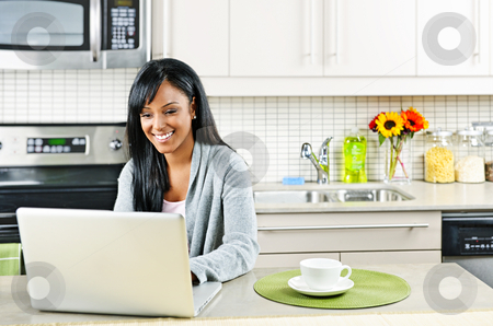 Woman using computer in kitchen stock photo, Smiling black woman using computer in modern kitchen interior by Elena Elisseeva