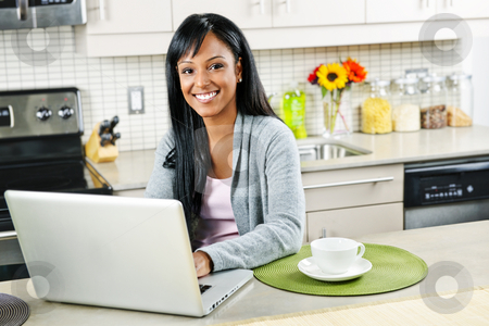Woman using computer in kitchen stock photo, Smiling black woman using computer in modern kitchen interior by Elena Elisseeva