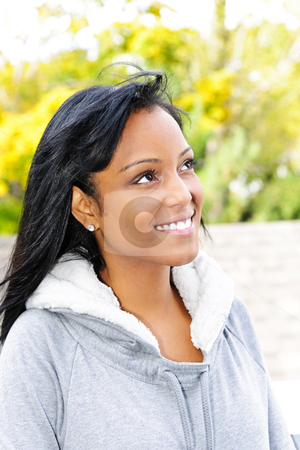 Portrait of smiling young woman outdoors stock photo, Happy young black woman looking to the side outdoors in fall by Elena Elisseeva