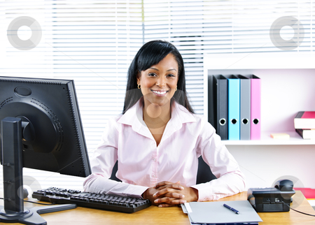 Smiling black businesswoman at desk stock photo, Portrait of smiling young black business woman at desk in office by Elena Elisseeva
