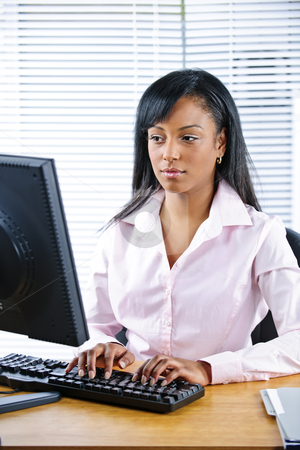 Serious black businesswoman at desk stock photo, Portrait of serious young black business woman at desk typing on computer by Elena Elisseeva