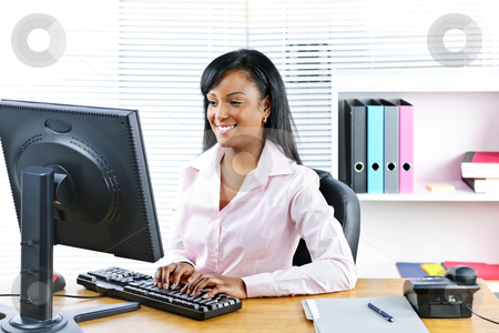 Smiling black businesswoman at desk stock photo, Portrait of happy black business woman at desk typing on computer by Elena Elisseeva