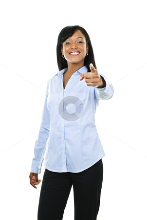 Smiling young woman pointing finger forward stock photo, Smiling black woman pointing finger at camera isolated on white background by Elena Elisseeva