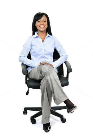 Businesswoman sitting in office chair stock photo, Young smiling black businesswoman sitting in leather office chair by Elena Elisseeva