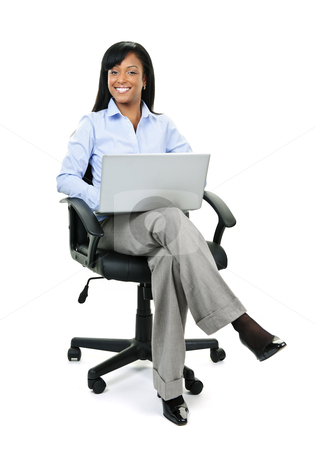 Businesswoman sitting in office chair with computer stock photo, Young smiling black business woman sitting in leather office chair with laptop computer by Elena Elisseeva